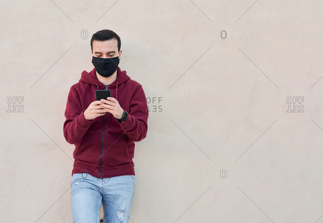 Young man with a mask writes on his phone on a yellow background