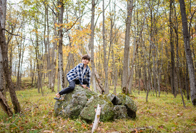 Young boy climbing on a large rock in the woods on a fall day.