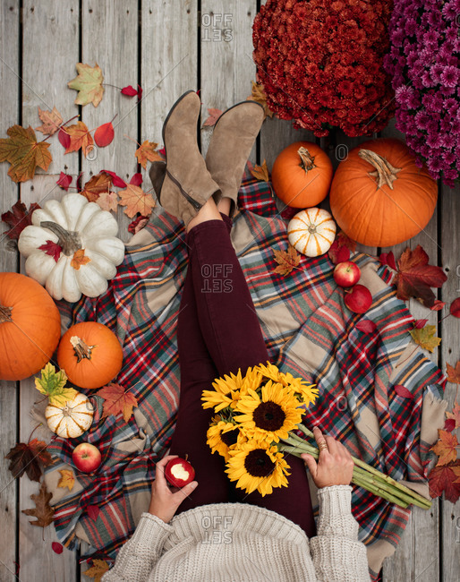 Overhead view of woman's legs and torso surrounded by fall items.