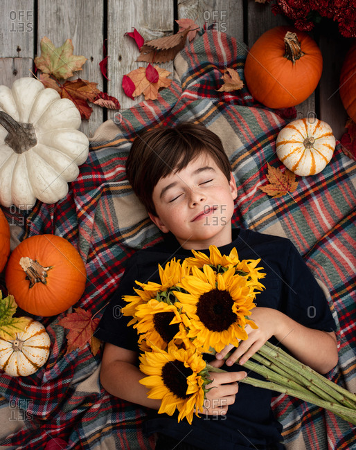 Overhead view of boy holding sunflowers surrounded by fall items.