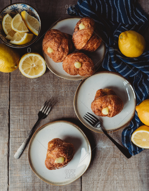 Overhead of lemon filled cruffins on wood table with plates and forks.