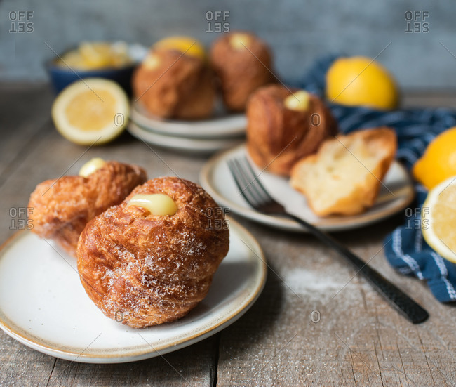 Lemon filled cruffins on wooden table with plates and forks.