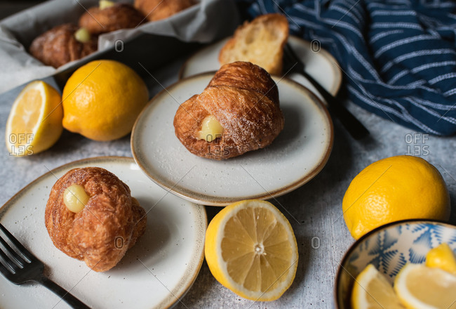 Lemon filled cruffins on stone counter with plates and forks.
