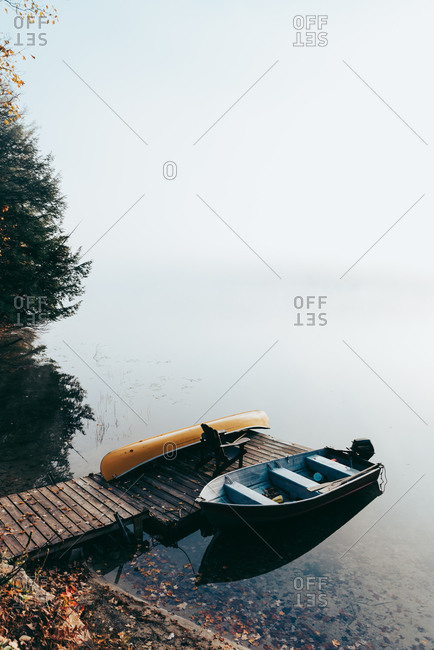 Empty dock with boats tied up on a foggy morning on a calm lake.