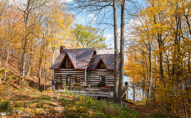 Log cabin cottage in the woods in Ontario, Canada on a fall day.