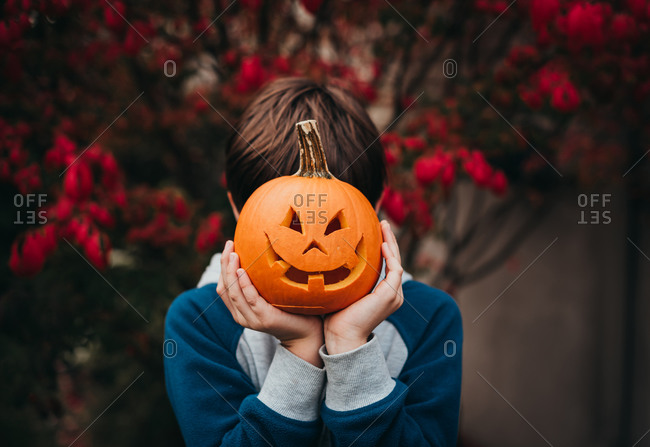 Young boy holding a mini jack-o-lantern over his face outdoors.