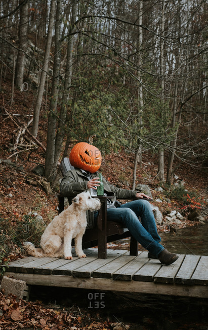 Man wearing scary pumpkin head for Halloween sitting on dock with dog.