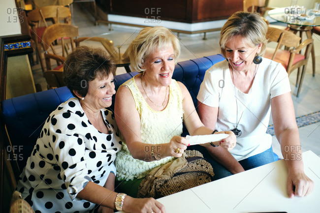 Older ladies enjoying relaxing and showing secret things to their friends