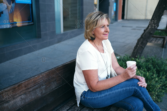 Woman drinking relaxed coffee enjoying the view on a bench in the street