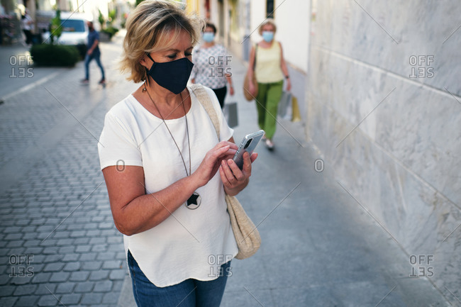 Woman looking at the phone and women walking around with their shopping