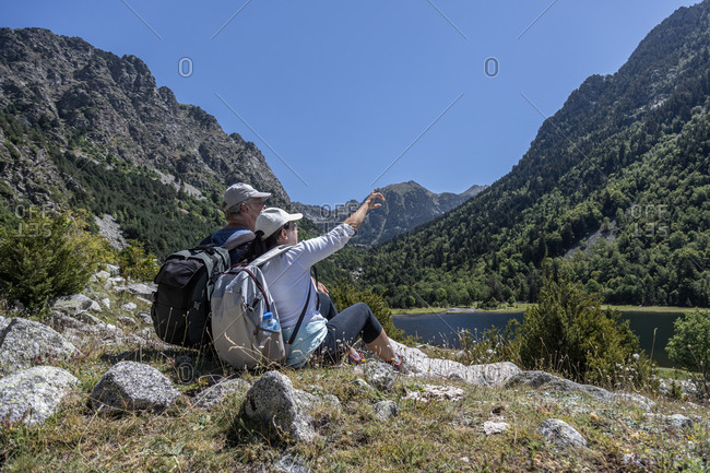 Side view of mid aged couple sitting on Spanish Pyrenees mountain and the woman points to the top