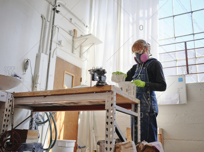Professional female sculptor working with plaster in her studio