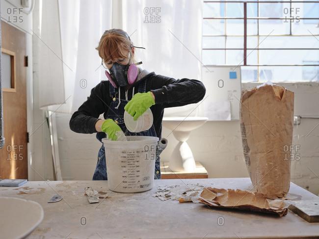Professional female sculptor mixing plaster in her studio