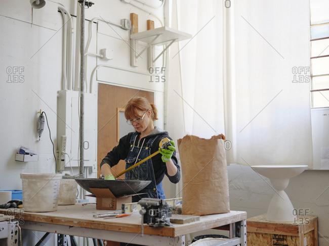 Professional female sculptor measuring her work in her studio