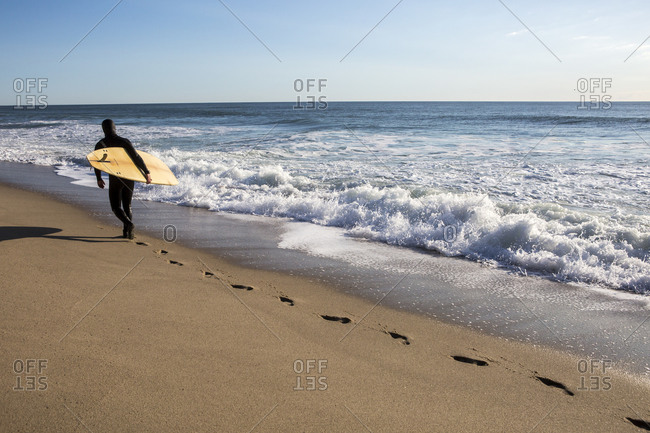 Wellfleet, MA, United States - June 2, 2017: A surfer in wetsuit from behind carrying surfboard at Whitecrest Beach