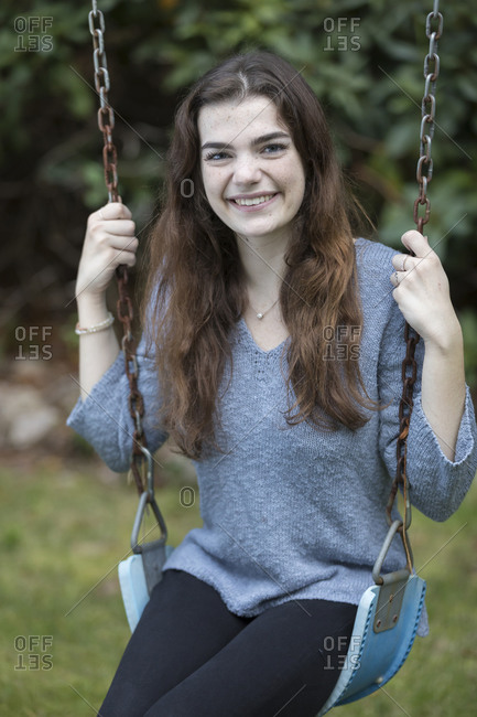 Pretty teen girl sitting on swing smiling with greenery in background