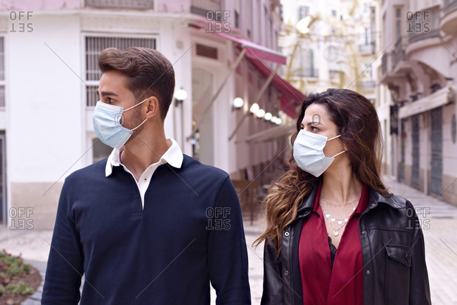 Young couple with face mask on the city streets