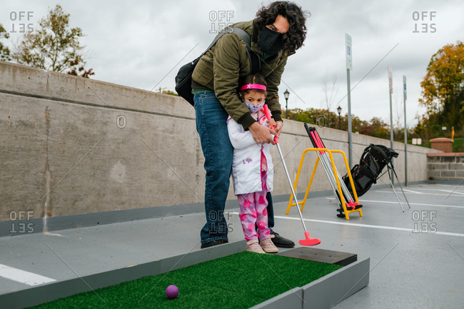 Father and daughter playing mini golf in halloween costume