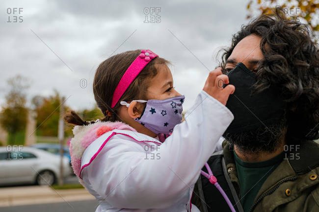 Little girl in halloween costume with dad wearing protective face mask
