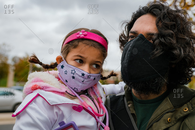 Father and daughter with protective face masks and halloween costume