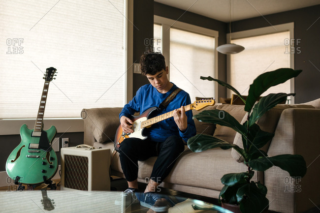 Teenager playing the guitar at home
