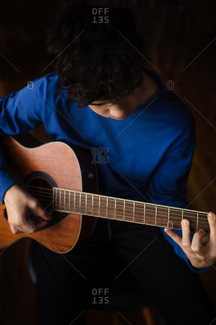 Teen buy plays acoustic guitar