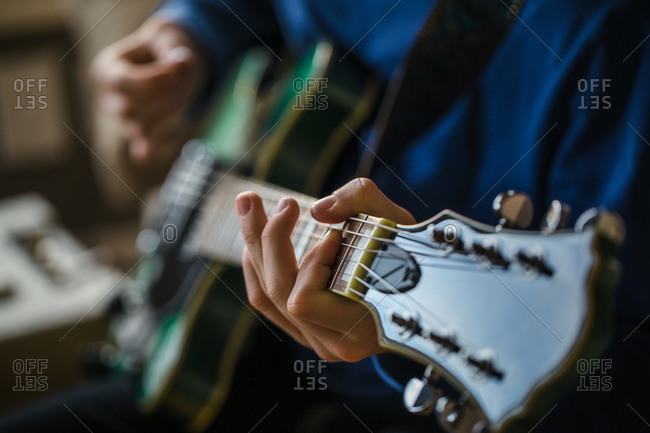 Close up of teen boy playing the guitar
