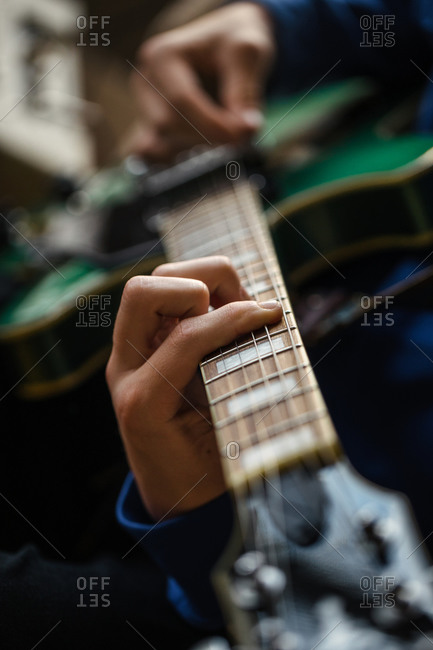 Close up of fingers, strings and frets of guitar