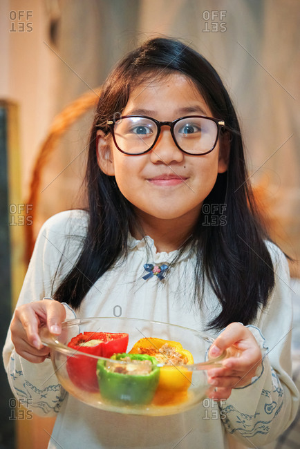 A girl showing her cooked colorful bell peppers in the glass bowl