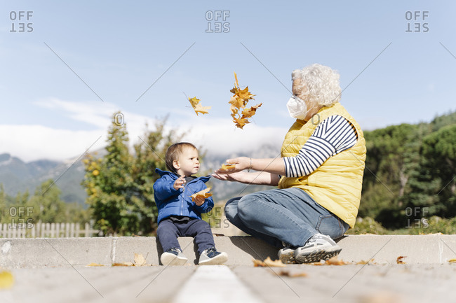 Grandmother wearing medical mask playing with leaves with her little grandson in a park