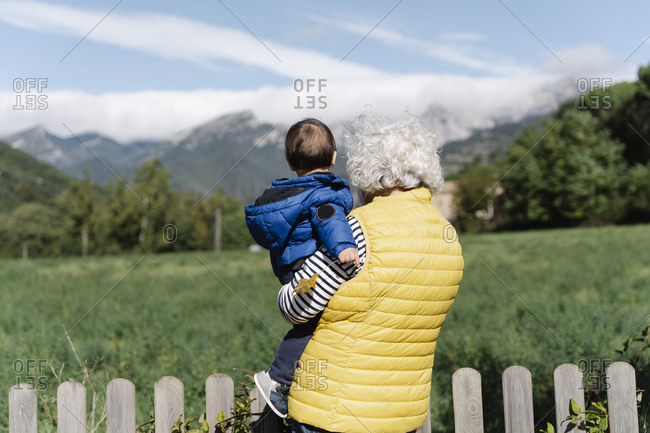 Rear view of a grandmother wearing a medical mask carrying her little grandson in a field