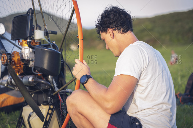 Young man controls the paramotor engine before starting a flight session.