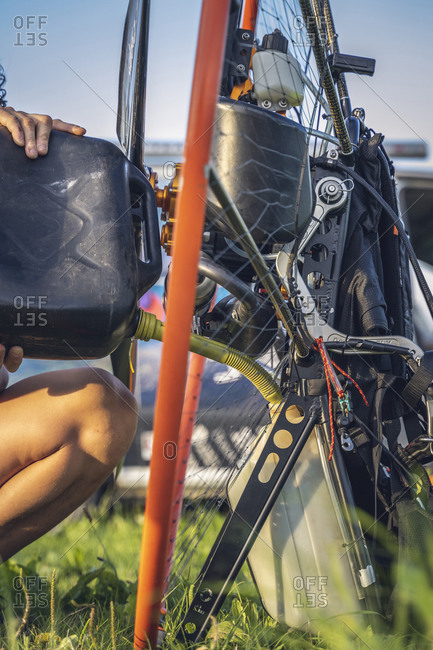 Young man fills the tank of the paramotor before starting a flight session. Detail.