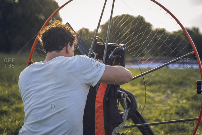 The young man checks the backpack attached to the paramotor, before starting a flight session.
