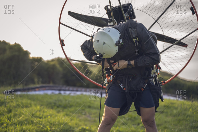 Young man, wearing a white helmet with an Action Cam on it, gets ready to fly with the Powered Paragliding ( Paramotor ) , and fastens his belt.