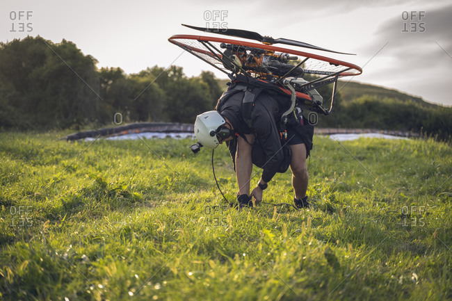 Young man, wearing a white helmet with an Action Cam on it, gets ready to fly with the Powered Paragliding ( Paramotore ) , and ties his shoes.