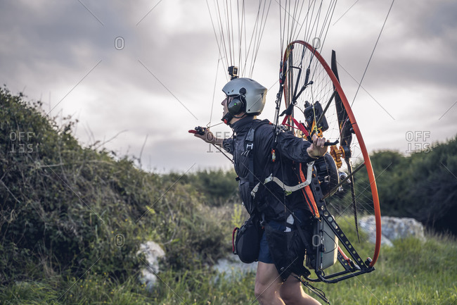 Young man, with the Powered Paragliding engine in his shoulders, runs on the lawn, and gets ready to jump and fly.