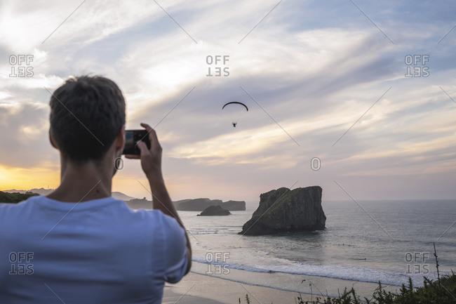 Man take a picture of paramotor pilot, on the beach.