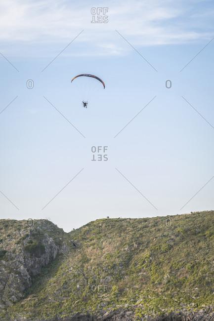 Llanes, Asturias, Spain - September 13, 2020: Pilot powered paragliding flying in Asturies