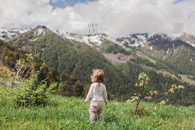 A little girl looks at the mountains with her back turned