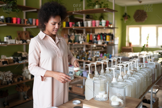 Black woman packing organic soap in store