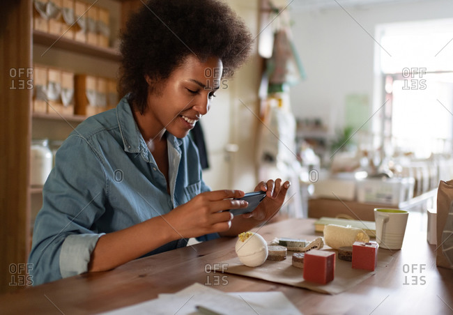 Cheerful black woman shooting natural cosmetic in store