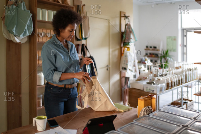 African American woman packing order in reusable bag