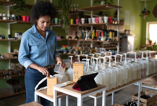 Black seller preparing online order in eco shop