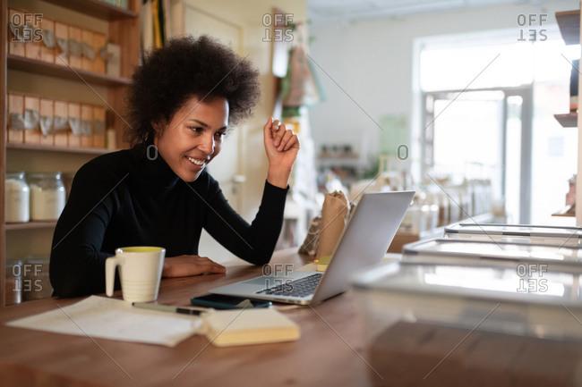 Happy black businesswoman teleworking in store