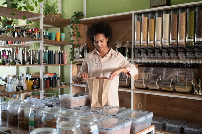 Mixed race woman using eco friendly packaging in shop