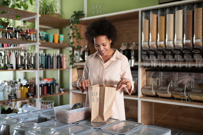 Happy black female checking groceries in paper bag