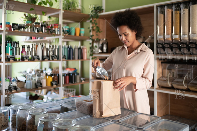 African American woman packing eco pasta in shop