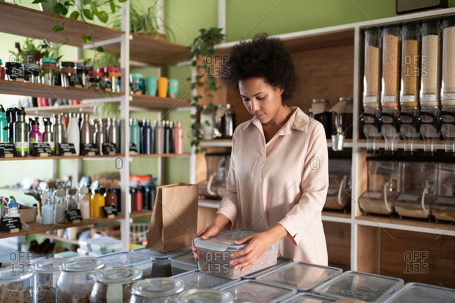 Mixed race woman working in zero waste shop
