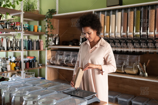 Black woman weighing organic product in shop